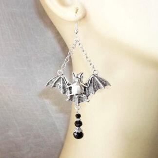 Steampunk oorbellen 18, vleermuis in zilveren kleur zijn zilverkleurige oorbellen met een vleermuis aan een ketting en een drie zwarte stenen.